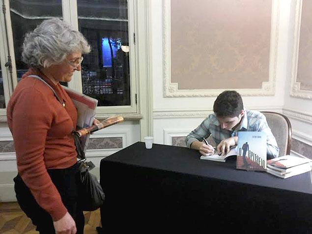 """Victhor assina um exemplar do livro """"O Epitáfio"""" na cerimônia de inauguração. Foto: Julia Reis"""