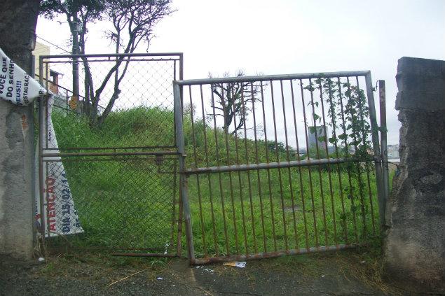 Material de construção, mato e água parada são problemas na escola.