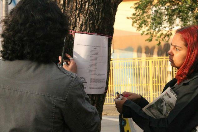 Público lê poemas expostos nas árvores (Créditos: Tamiris Gomes)