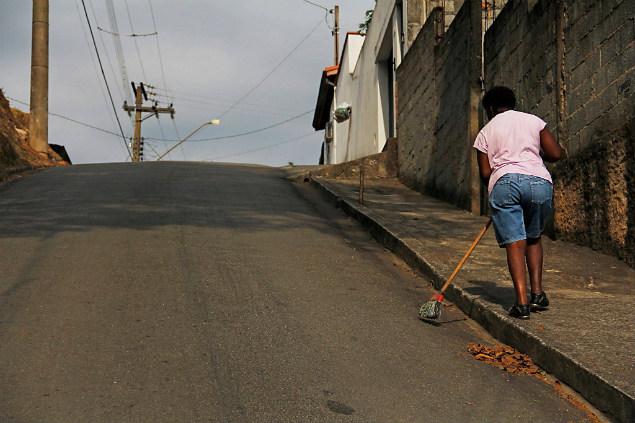 Moradora varre a rua em Caieiras, na GSP. Falta de água atinge bairros da cidade (Foto: Mariana Lima/Divulgação)