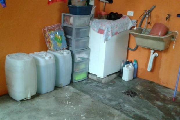 Moradora  do Jardim Valéria armazena a água em galões para se preparar para os dias sem água. (Foto: Daniele da Silva/Divulgação)