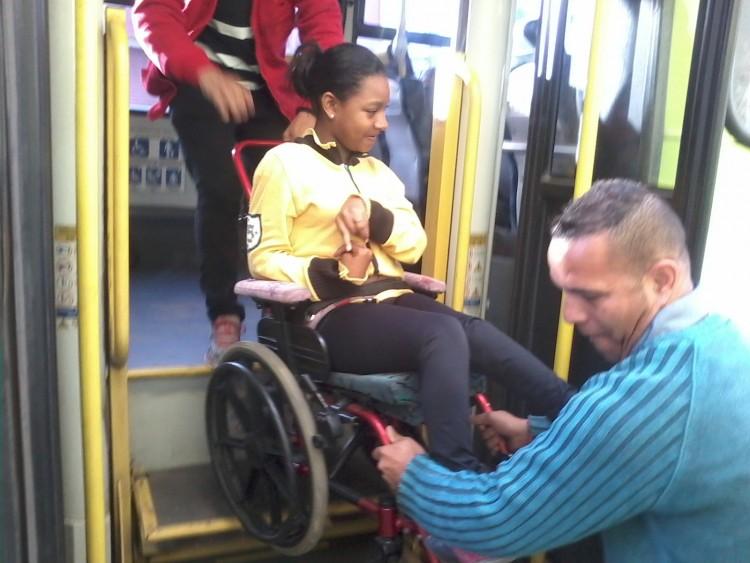 Passageiro ajuda judando, com as mãos, mãe de Juliana a subir a cadeira de rodas pelo elevador quebrado