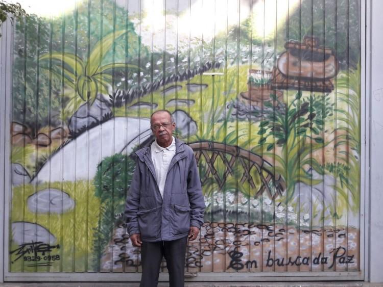 """Seu Leó em frente ao grafite que registra a sua trajetória: """"Em busca de paz"""""""